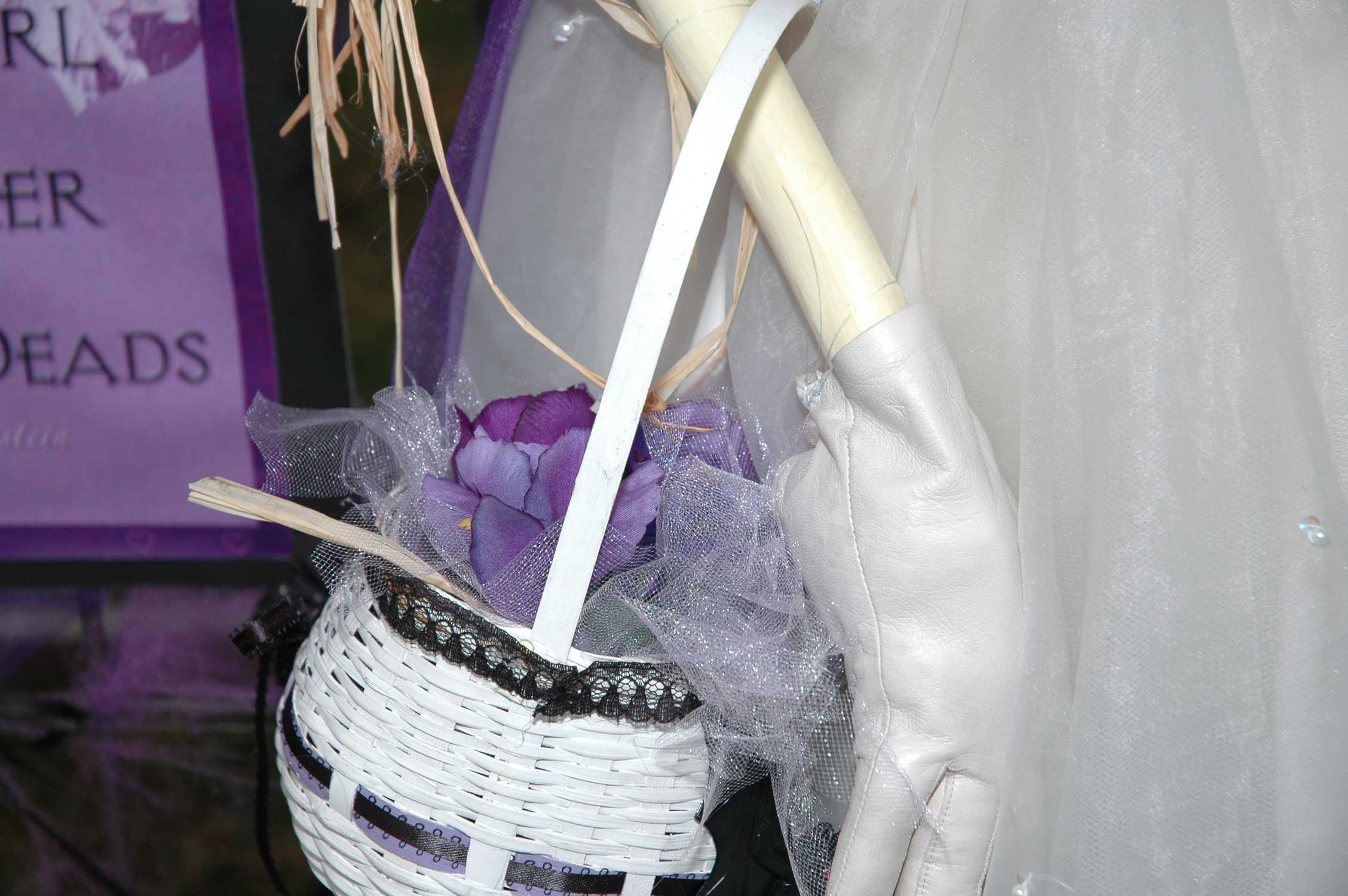 Our flower girl wears gloves and carries a basket of purple flowers.